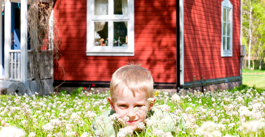 Familien Ferien in Schweden Junge vor Blockhütte